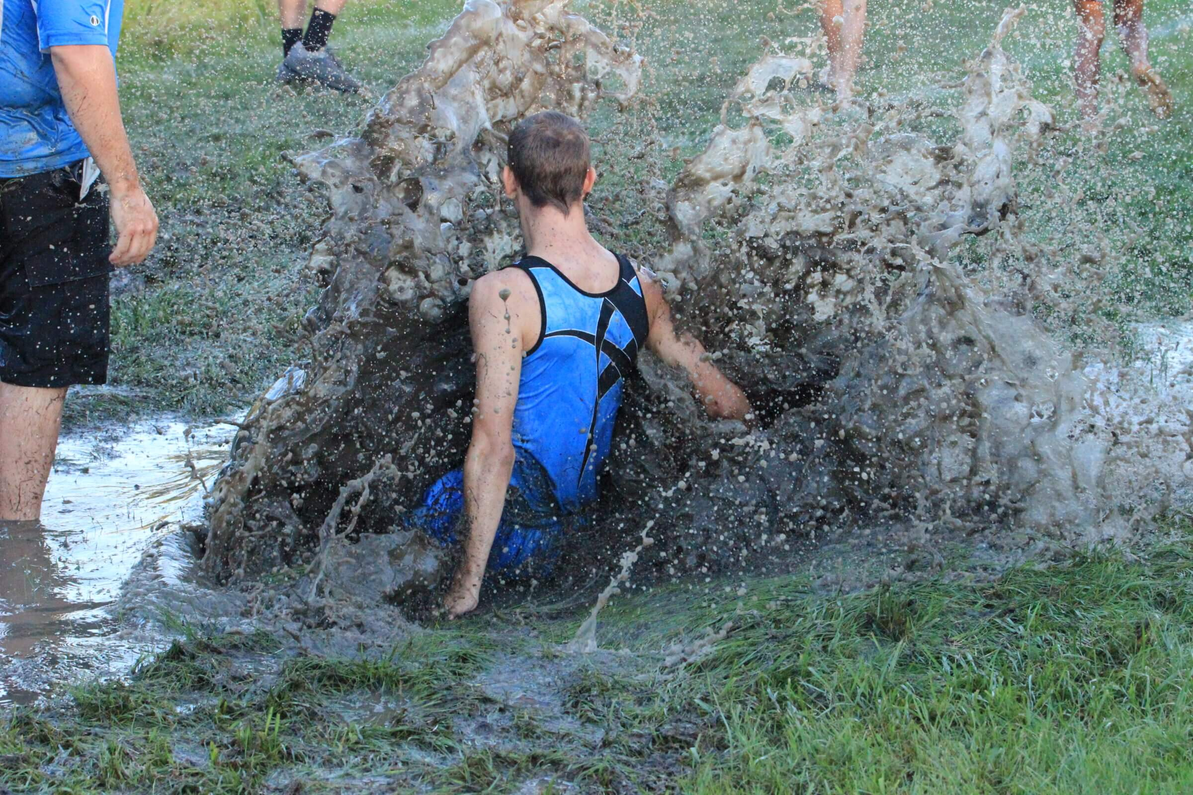 A TigerHawk cross country runner splashing into water
